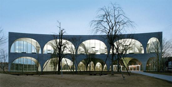 """伊東豊雄が設計した東京八王子市の多摩美術大学図書館。コンクリート壁がアーチ型に大胆に展開され、開放的で軽快なイメージを生かした。内部にはやわらかい曲線型の本棚などを置いて""""芸術的インスピレーションをあたえる図書館""""を追求した。(写真=プリツカー賞ホームページ)"""