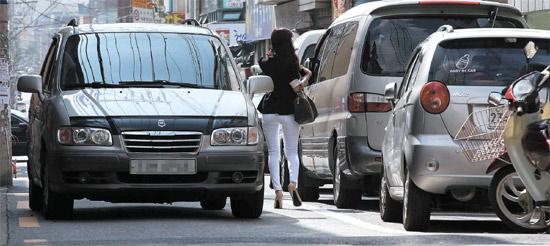 15日、ソウル江西区禾谷1洞の道路で女性が向かってくる車と駐車した車の間を歩いている。この道路は歩道と車道が区分されていない幅9メートル未満の生活道路だ。