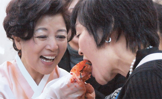 昨年12月7日、東京の韓国大使館で開かれたキムジャン(キムチ作り)お祭りで、李丙ギ大使の夫人シム・ジェリョン氏(左)が安倍首相の夫人昭恵氏にキムチを食べさせている。この日、李大使は和食とキムジャン文化がユネスコ人類無形遺産に登録されたことに言及し、両国が互いに配慮するべきだと強調した。(写真=中央フォト)