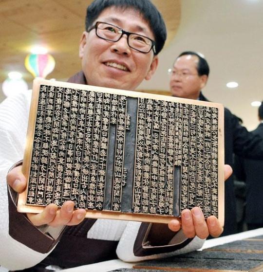 19日、清州市の古印刷博物館の金属活字鋳造展示館で開かれた「直指金属活字復元事業結果報告会」で林氏が復元された「直指」の金属活字を手にしている。