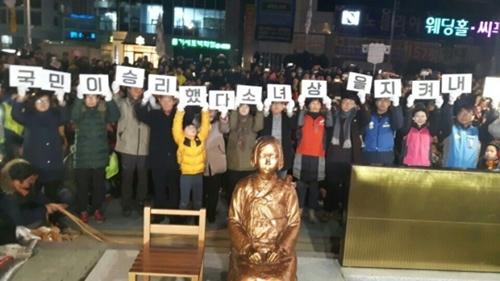 2016年12月31日午後9時、釜山市東区の日本領事館前に設置された平和の少女像の周りで釜山市民らが「国民の勝利だ」「少女像を守り抜こう」というピケットを手にしている。(写真=釜山警察庁)