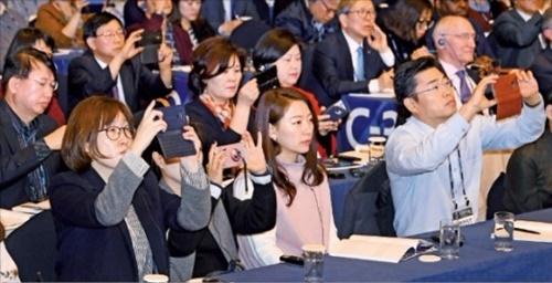「グローバル人材フォーラム2017」基調セッションに参加した人たちが発表内容をスマートフォンで撮影している。