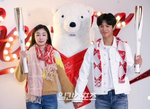 1日午前、ソウル弘大前でコカコーラの平昌冬季五輪体験イベント行事に参加し、聖火を持ってポーズを取っているキム・ヨナ(左)とパク・ボゴム。