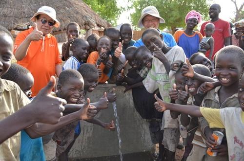 2013年6月、セネガルでKOICA海外奉仕団員と住民らが飲用水開発事業で作られた飲料水台できれいな水が出てくるのを喜んでいる。(写真=KOICA提供)