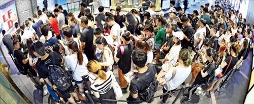 中国人の購入代行者「代工」が化粧品など人気免税品を購入するため14日、ソウル小公洞のロッテ免税店前で営業開始前に列をつくっている。「代工」は昨年の中国のTHAAD(高高度防衛ミサイル)報復後、中国人団体観光客の代わりに韓国免税店の主な顧客になった。
