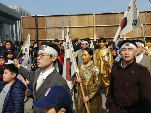 京畿道広州のパバル劇会の団員が光化門広場で独立活動家と日本軍の対立の様子を再演したパフォーマンスをする傍らで市民が記念撮影をしている。
