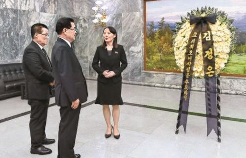 北朝鮮の金与正労働党第1副部長が12日に板門店北側地域の統一閣で青瓦台の鄭義溶国家安保室長(右から2番目)と民主平和党の朴智元議員に李姫鎬氏を追悼して送った金正恩国務委員長の弔花を伝えている。(写真=統一部)