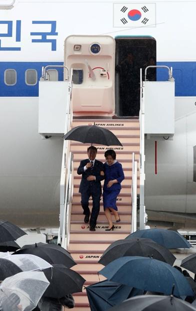韓国の文在寅大統領が大阪で開かれるG20サミット(28~29日)に参加するために27日、日本を訪問した。雨が降る中、関西国際空港に到着した文大統領が金正淑夫人と傘を差して専用機から降りている。(写真=青瓦台写真記者団)