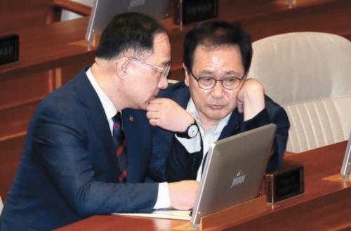 洪楠基(ホン・ナムギ)副首相(左)と兪英民(ユ・ヨンミン)科学技術情報通信部長官が4日、国会で対話している。洪副首相は日本の輸出規制について「明白な経済報復であり、相応の措置を用意する」と述べた。