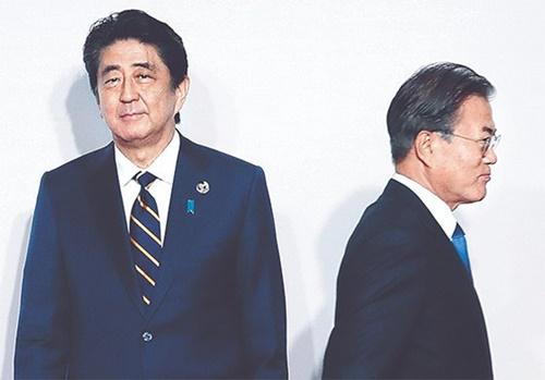 韓国の文在寅(ムン・ジェイン)大統領が28日、大阪20カ国・地域(G20)首脳会議(サミット)の歓迎式で安倍晋三首相(左)と8秒間握手した後、移動している。[青瓦台写真記者]