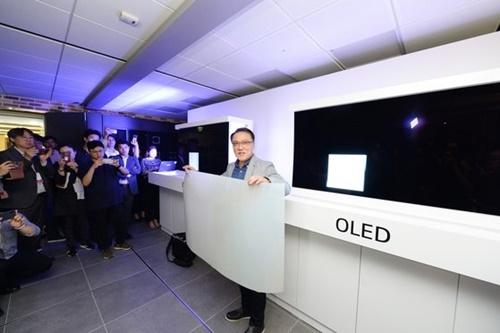 17日、ソウル汝矣島ツインタワーでナム・ホジュン研究所長(専務)がサムスンQLEDテレビに付けられた量子ドットシートを持っている。キム・ヨンミン記者