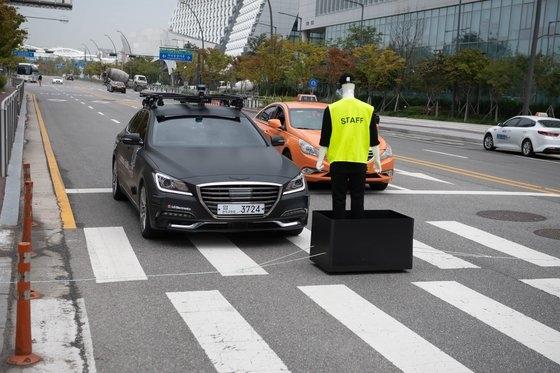 LG U+が10日午前、ソウル麻谷LGサイエンスパークで5G-V2X自動協力運転を試演している。写真は歩行者(マネキン)が急に飛び出した状況で車が停止する場面[写真 LG U+]