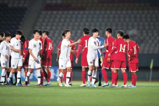 紆余曲折の末29年ぶりに実現した男子サッカーの平壌(ピョンヤン)南北対戦が0-0の引き分けで終わった。5日、平壌金日成競技場で行われた試合の後、あいさつを交わす南北代表選手。[写真 大韓サッカー協会]