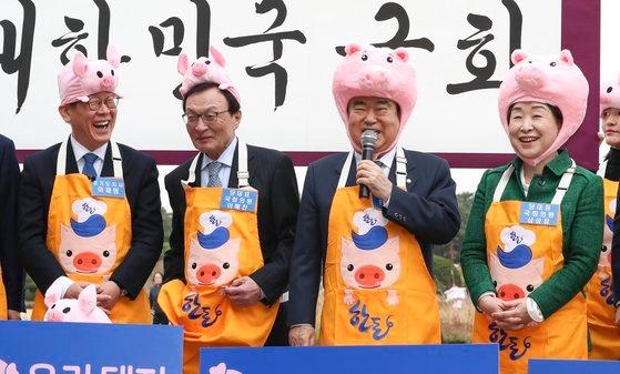 文喜相国会議長(右から2番目)が12日午後、国会議員会館の前で開かれた「2019国会ウリハンドン愛キャンペーン」で豚帽子をかぶって挨拶の言葉を述べている。左から李在明・京畿知事、民主党の李海チャン(イ・ヘチャン)代表、文議長、正義党の沈相ジョン(シム・サンジョン)代表。イム・ヒョンドン記者