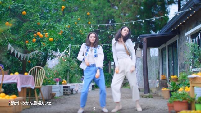 済州のみかん農場カフェを背景に日本人モデルが踊る新しい韓国観光公社のCMの場面[写真 imagine your korea]