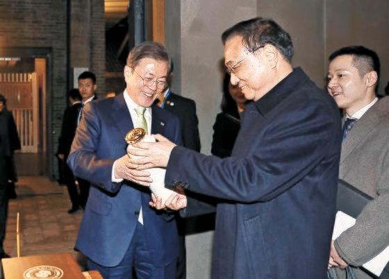 韓国の文在寅大統領が23日、中国四川省成都の水井坊博物館で、中国の李克強首相から特注の白酒を贈り物として受け取っている。[写真 青瓦台写真記者団]