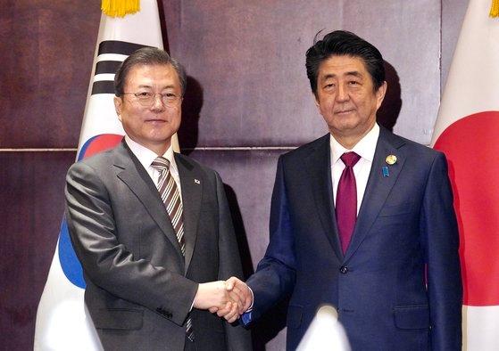 第7回韓日中首脳会議に出席するために中国四川省成都を訪問した韓国の文在寅大統領(左)が昨年12月24日(現地時間)、日本の安倍晋三首相と会って握手している。[写真 青瓦台写真記者団]
