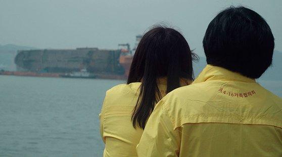 セウォル号を題材にしたドキュメンタリー映画『不在の記憶』で海の上の船を眺めている遺族の後ろ姿。イ・スンジュン監督は「編集をしているうちにふと止めておいた映像の中の子供たちの表情を見る時、最もつらかった」と話した[写真 EBS国際ドキュメンタリー映画祭]