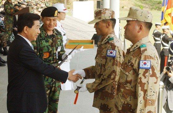 2003年4月28日、イラク派兵申告および歓送行事に参加した盧武鉉元大統領が徐熙(ソヒ)部隊のチェ・グァンヨン大佐に指揮棒を手渡している。[中央フォト]