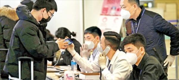 <国内連絡先確認後に入国>5日に仁川国際空港第1ターミナルで中国発の飛行機に乗って到着した乗客が検疫台で韓国国内の連絡先の確認を受ける手続きを踏んでいる。検疫要員が電話をかけて入国者の国内所在が把握できるかを確認する。キム・ヨンウ記者