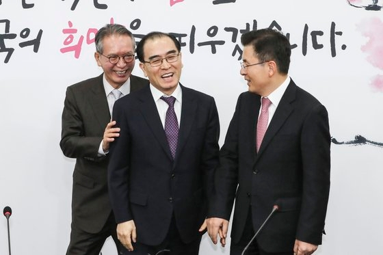 太永浩元駐英北朝鮮公社(中央)が11日、国会で自由韓国党入党と4・15総選挙で地方区出馬を発表する記者会見を行い、黄教安代表と挨拶している。左はキム・ヒョンオ公認管理委員長。キム・ギョンロク記者