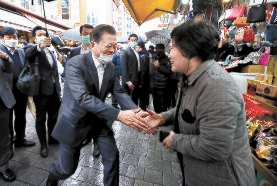 12日、ソウル南大門市場を訪問して商人と握手をしている文在寅大統領。[写真 青瓦台写真記者団]