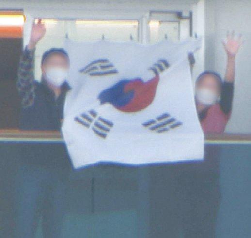 新型コロナ集団感染が発生したクルーズ船「ダイヤモンド・プリンセス」号に隔離された在日同胞60代女性Kさん(右)が夫と共にベランダに掲げた太極旗を持ち上げている。ユン・ソルヨン特派員