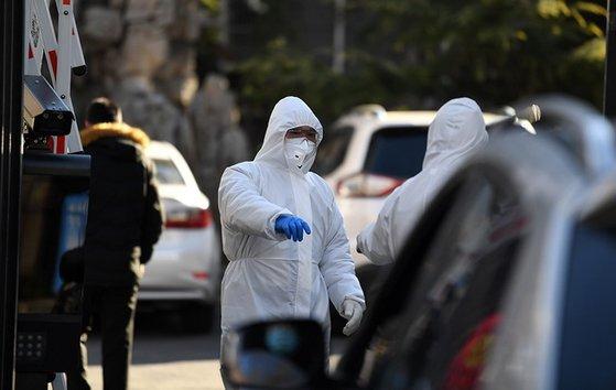 北京市内でも新型コロナ防止のために防護服を着て体温を測定する姿が日常になっている。[中国人民網 キャプチャー]