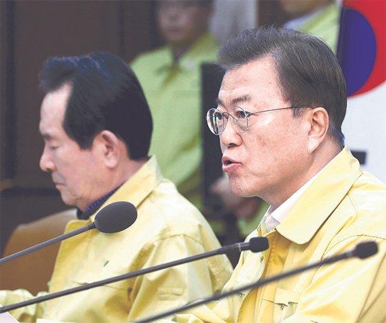 文在寅大統領(右)が23日午後、政府ソウル庁舎で「コロナ19汎政府対策会議」を主宰してコロナ19危機警報を「深刻」段階に格上げした。[写真 青瓦台写真記者団]