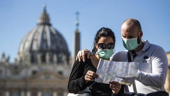 マスクをつけてバチカン・サンピエトロ広場前で地図を見るイタリア観光客