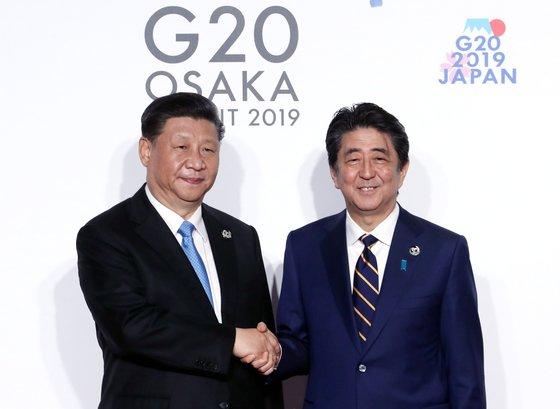 習近平中国国家主席(左)が昨年6月28日午前、インテックス大阪で開かれた20カ国・地域(G20)首脳会議(サミット)公式歓迎式で議長国の安倍晋三首相と握手を交わしている。[写真 青瓦台写真記者団]
