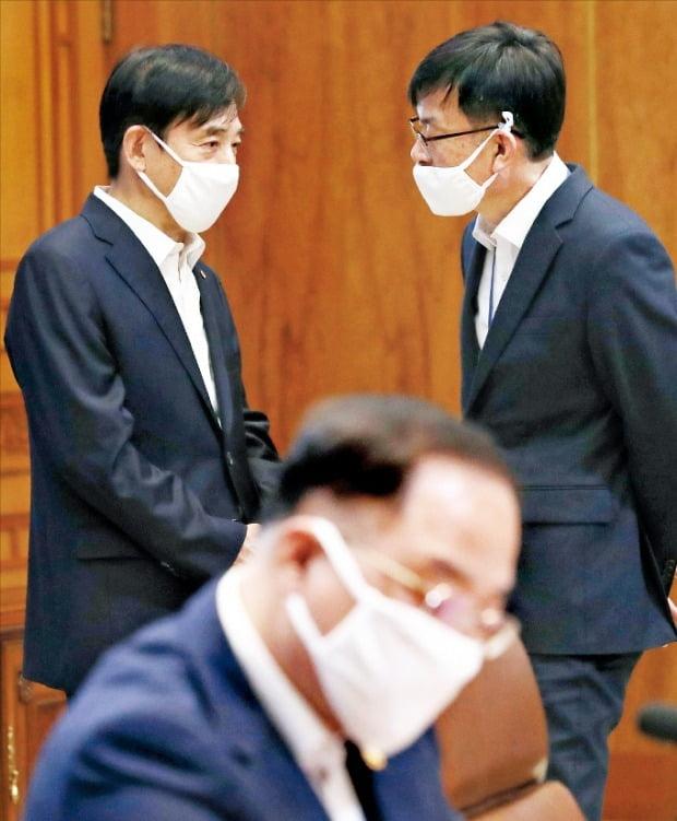 19日に青瓦台で開かれた新型肺炎対応を協議するための非常経済会議に先立ち、韓国銀行の李柱烈(イ・ジュヨル)総裁(左)と青瓦台の金尚祖(キム・サンジョ)政策室長が対話している。中央は洪楠基副首相兼企画財政部長官。ホ・ムンチャン記者