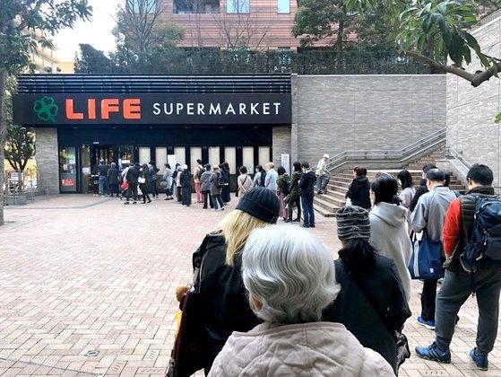 25日、東京のある大型スーパーの前に、食料品を買い求める人々列をつくっている。