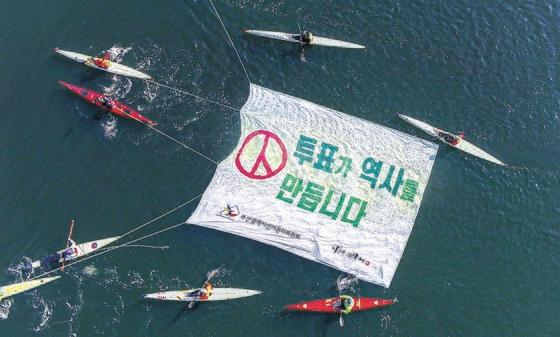 今月15日、釜山(プサン)選挙管理委員会が海雲台(ヘウンデ)センタムシティ付近の水營江(スヨンガン)でカヤック同好会のメンバーたちとともに4・15総選挙の投票参加を呼びかけるパフォーマンスを行っている。[写真 釜山選挙管理委員会]