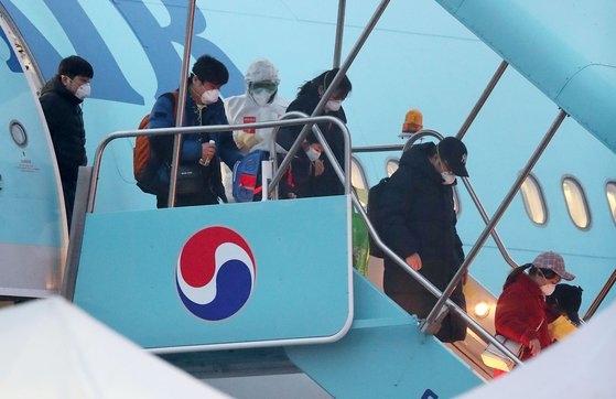 2月12日、中国湖北省武漢地域に滞留していた韓国海外同胞と中国人家族がソウル金浦(キンポ)国際空港に到着して大韓航空チャーター機から降りている。キム・ソンニョン記者