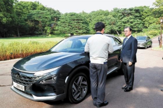 文在寅(ムン・ジェイン)大統領が青瓦台(チョンワデ、大統領府)で大統領専用車として導入した燃料電池車(ネクソ)について説明を聞いている。[青瓦台]