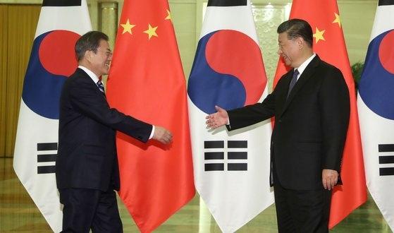 韓国の文在寅大統領(左)が昨年12月、中国北京人民大会堂で中国の習近平国家主席(右)との首脳会談に先立ち握手をしようとしている。[写真 青瓦台写真記者団]