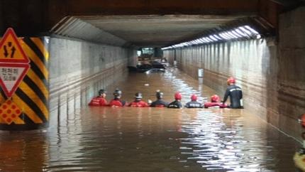 23日の豪雨で浸水した釜山市東区の草梁地下車道で救助隊員が救助作業をしている。[写真 釜山警察庁]