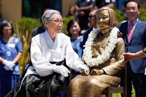 旧日本軍慰安婦被害者の故金福童(キム・ボクドン)さんが少女像に触れている。[中央フォト]