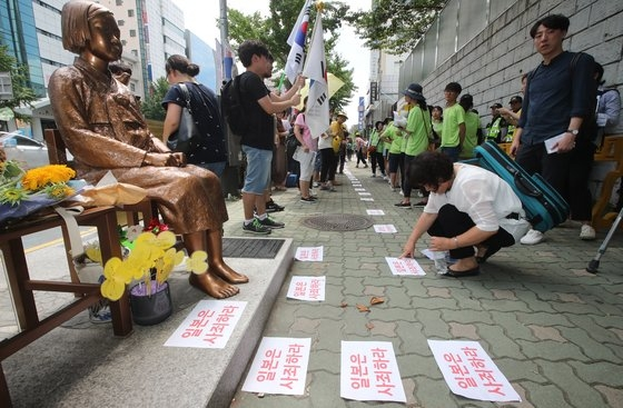 昨年8月14日午後、釜山東区の日本総領事館前「平和の少女像」で開かれた「旧日本軍慰安婦被害者をたたえる日記念 釜山第44回水曜デモ」に出席した釜山地域の市民社会団体メンバーが少女像から労働者像までハンドピケをリレーするパフォーマンスをしている。ソン・ポングン記者