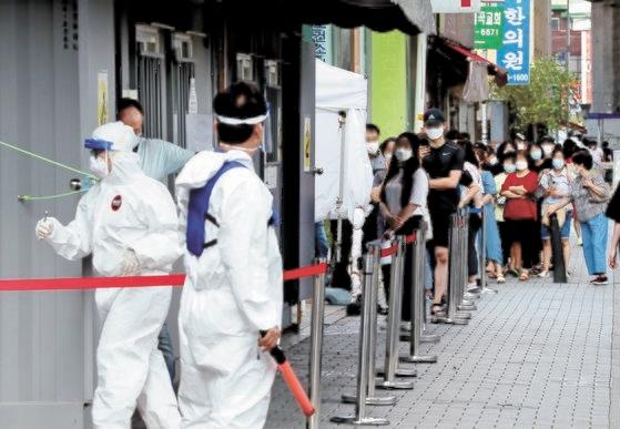 ソウル城北区(ソンブクク)の保健所選別診療所で市民が検査を受けるために列に並んでいる。