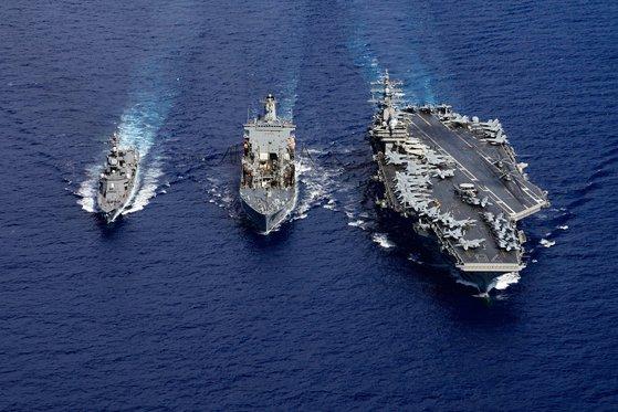 日本と米国が15~18日、東シナ海で空中・海上実動演習を進めている。右側は米軍の原子力空母「ロナルド・レーガン」。[写真 海上自衛隊ツイッター]