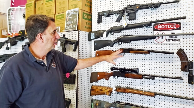 米ワシントン近隣のバージニア州で銃器販売店を経営するブレイナーさんが記者に銃器を説明している。 チュ・ヨンソク特派員