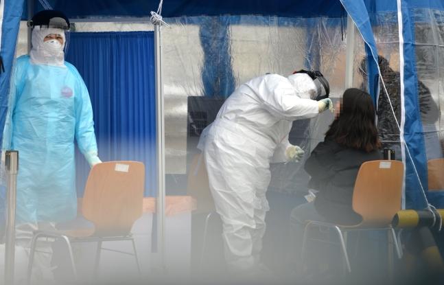 11日、大田(テジョン)のあるハンバッ体育館駐車場に用意された新型肺炎臨時選別診療所で医療スタッフが訪問した市民を検査している。[中央フォト]