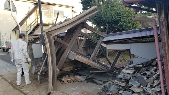14日午後、福島県桑折町で、ある住民が地震で倒壊した家を見ている。この家には20年前から人が住んでいないため、地震によるけが人はなかった。ユン・ソルヨン特派員