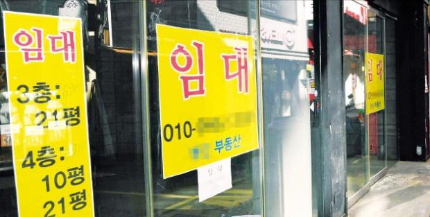 新型コロナウイルス流行の余波で明洞などソウルの主要商圏が崩壊した。明洞通りの空き店舗前を市民が通り過ぎている。シン・ギョンフン記者