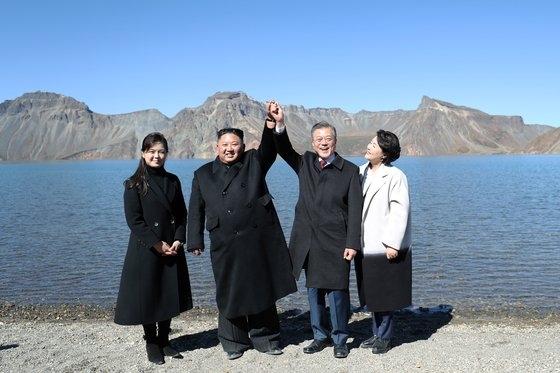 韓国の文在寅(ムン・ジェイン)大統領(右から2人目)と金正淑(キム・ジョンスク)夫人(右から1人目)、北朝鮮の金正恩(キム・ジョンウン)国務委員長(左から1人目)と李雪主(リ・ソルジュ)夫人(左から1人目)が2018年9月、白頭山(ペクドゥサン)天地に立って記念撮影に臨んでいる。[平壌(ピョンヤン)写真共同取材団]