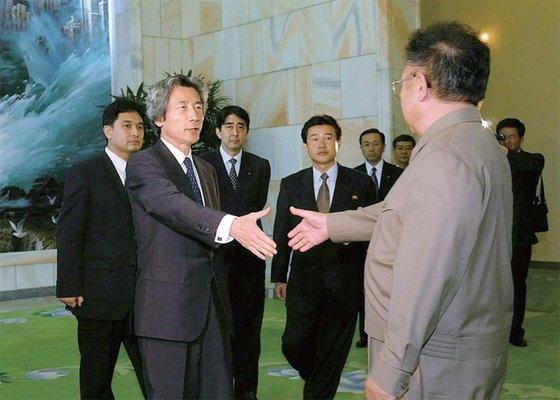 2002年9月に訪朝した小泉純一郎首相(当時、写真左)が、金正恩国防委員長(右)に会い、握手している。後方に安倍晋三官房長官(当時)も立っている。[中央フォト]