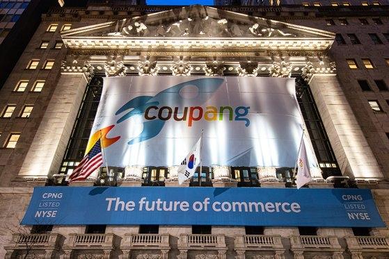 ニューヨーク・ウォール街の中心になびく太極旗。クーパンの上場を控え、米国ニューヨーク証券取引所の建物にクーパンのロゴと共に太極旗が掲揚された。[写真 クーパン]