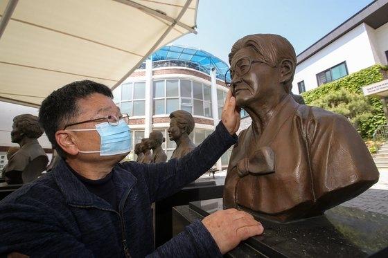 今月2日、京畿道広州市退村面(キョンギド・クァンジュシ・テチョンミョン)の福祉施設「ナヌムの家」を訪れた故イ・ヨンニョさんの息子ソ・ビョンファさんがヨンニョさんの胸像の顔に触れている。ウ・サンジョ記者